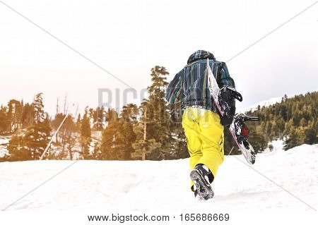 snowboarder walking against snowy mountains and blue sky