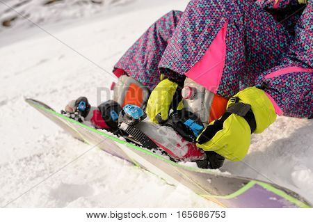 girl sitting on the ski slopes and snowboard boots buttons