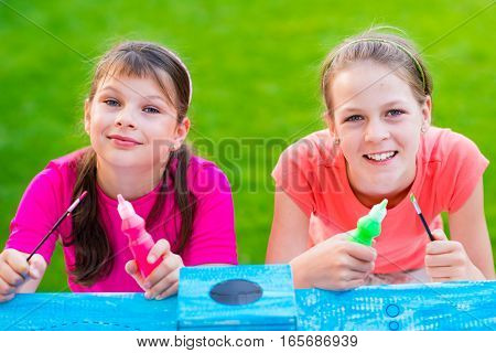 Young Girls Painting Cardboard House In the Garden - shallow depth of field