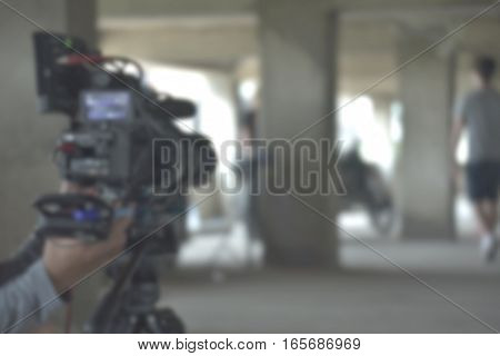 blurred background of videographer working wiht Professional equipment video camera shooting movie cinema video for broadcast TV television