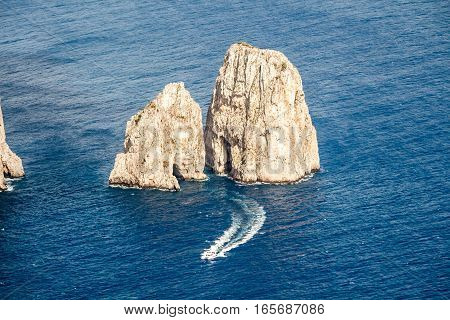 Dangerous cliff rocks rises from the sea. Two hight cliff rocks with grottos rising above a deep blue water. Small motor yacht passing it by.