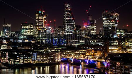 Big city towers at night with lights and reflections in the river. Modern big city tall skyscrapers in the industrial business city at night. Capital of finances City of London at night. Long and curvy lights reflections in the river Thames.