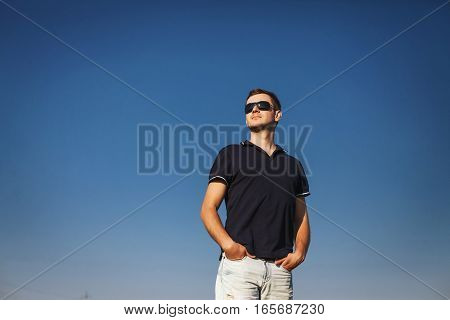 man with glasses stands proudly and looks into the distance over blue sky