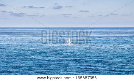 Sailing yacht among sky-blue currents. A lone white sail steadfastly glistens through azure mists afar at sea.