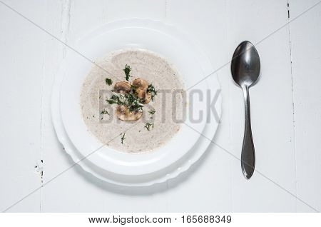 Bowl of creamy mushroom soup on wood.