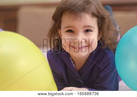 Smiling cute little girl lying on bed with balloons