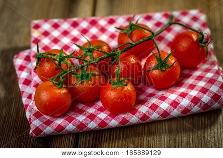 Red cherry tomatoes on an old wooden table in rustic style