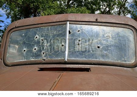 The windshield of an old rusty pickup is riddled with bullet holes from a rifle.