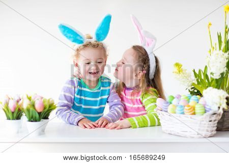 Happy children celebrate Easter at home. Boy and girl wearing bunny ears enjoying egg hunt. Kids playing with color eggs and flower basket. Spring crafts and art for toddler child and preschooler kid.