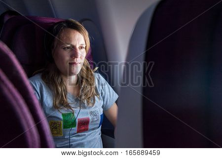 Attractive female passanger watching in-flight entertainment. Tourist sitting in airplane.