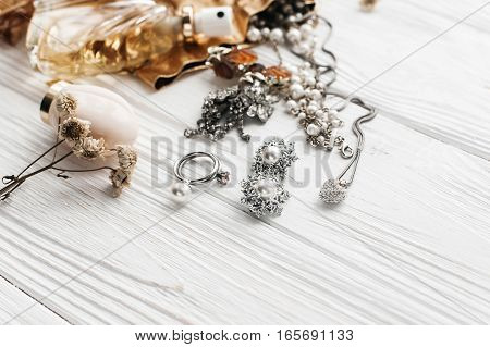 Luxury Expensive Jewelry Rings Earrings And Perfume On White Rustic Wooden Table With Space For Text