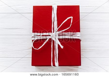 Stylish Red Present Top View On White Rustic Wooden Background. Happy Valentine Day Card Or Birthday