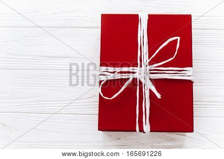 Top View Of Stylish Red Present On White Rustic Wooden Background. Happy Valentine Day Card Or Birth