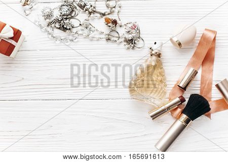 Luxury Expensive Jewelry And Make Up Essentials And Perfume Flat Lay On White Rustic Wooden Table Wi
