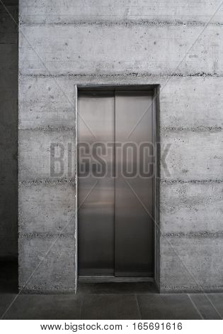 Modern elevator in minimalist concrete building, concrete core of building with elevator, stainless steel elevator in basement