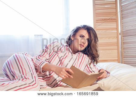girl in pajamas lying on the bed and reading a book holiday