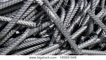 Curved deformed steel bars (bent division rebar). Those metal rods are used as armature to reinforce concrete in buildings. The closeup is ideal for backgrounds.