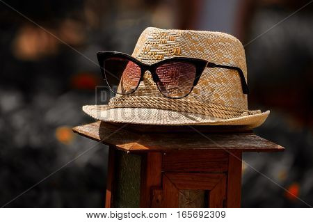 The picturebackgroudtexture of the straw hat with red glassesspectacles on the lamp in dark tones into wild nature