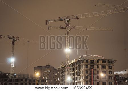 construction cranes on the construction site at night
