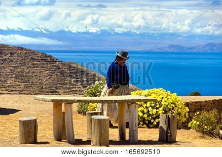 ISLA DEL SOL BOLIVIA - AUGUST 18: Indigenous woman on Isla del Sol Bolivia with the Cordillera Real of the Andes Mountains in the background on August 18 2014