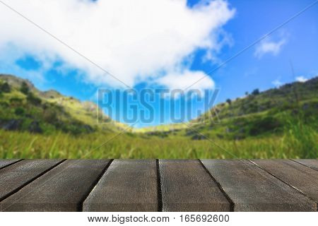 Wood plank on natural green grass field & sky background with farmer cottage- can use for display or montage your products