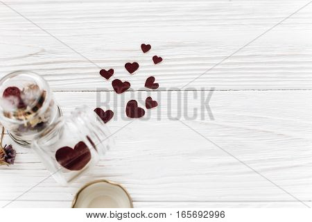 Happy Valentine Day. Stylish Hearts In Glass Jar And Roses  On White Wooden Background. Unusual Card