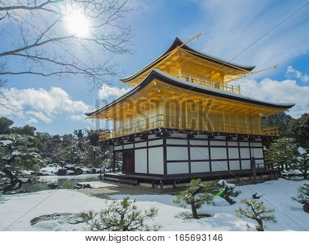 Golden Pavilion of Kinkakuji Temple with snow falling and blue sky background at Kyoto, Japan.