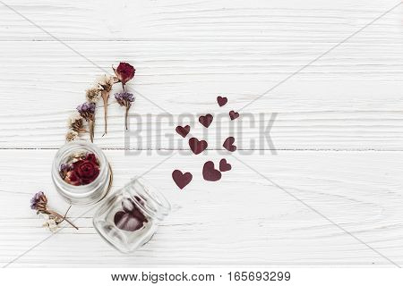 Stylish Hearts In Glass Jar And Roses Flat Lay On White Wooden Background. Happy Valentine Day. Unus
