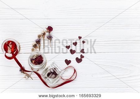Stylish Hearts In Glass Jar And Roses And Ribbons On White Wooden Background. Unusual Happy Valentin