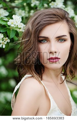 Beautiful Woman with Wavy Hair on Spring Blossom Background