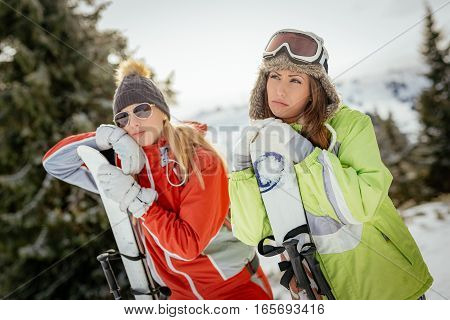 Beautiful young woman friends in winter vacations. They standing with skis and looking away with boring face.