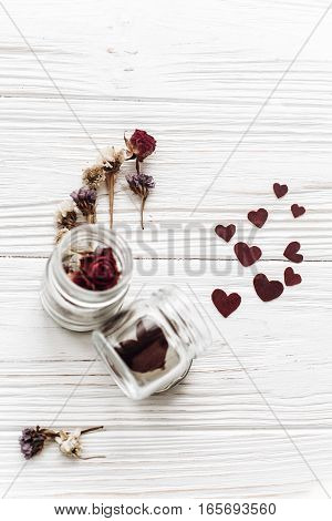 Stylish Hearts In Glass Jar And Roses On White Wooden Background. Happy Valentine Day. Unusual Greet