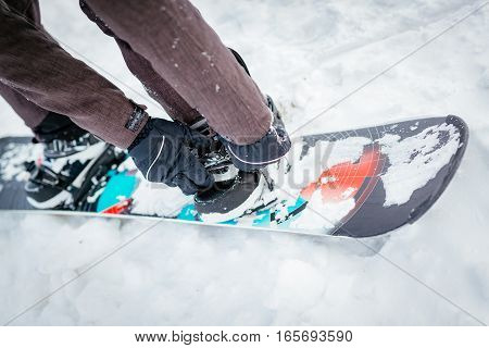 Close-up of man hands adjusting bindings on snowboard boot.