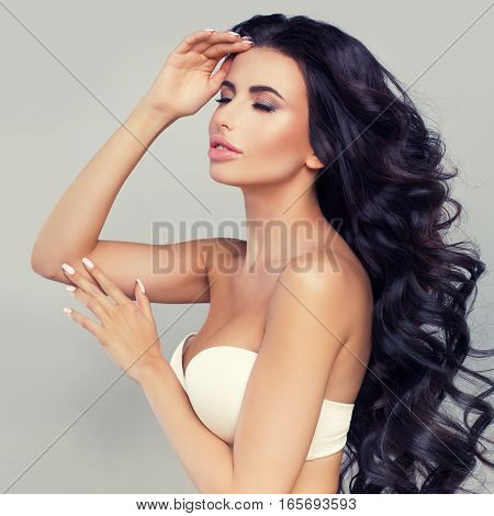 Relaxing Woman with Long Dark Hair and Natural Makeup. Cute Fashion Model