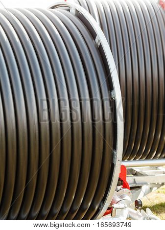 Machines production concept. Detailed closeup of dark flexible plastic hose pipes.