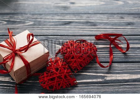 Valentine Concept. Stylish Red Present And Two Heart Ribbons On Black Rustic Wooden Background. Happ
