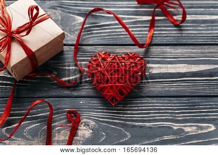 Valentine Concept. Stylish Red Present And Heart Ribbons On Black Rustic Wooden Background. Happy Va