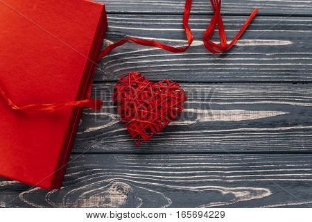 Happy Valentine Day Card Concept. Stylish Red Present And Heart Ribbons On Black Rustic Wooden Backg