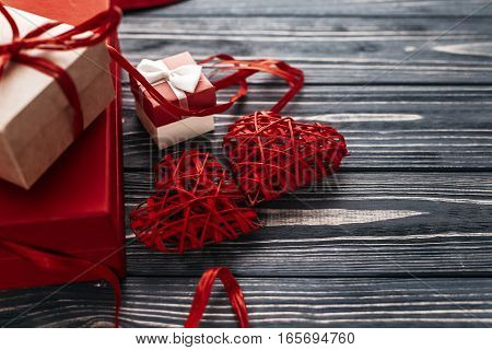 Stylish Red Present And Two Heart Ribbons On Black Rustic Wooden Background. Happy Valentines Day Co