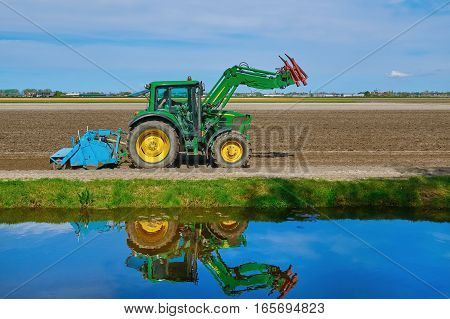 Tractor in a Plowed Field near the River