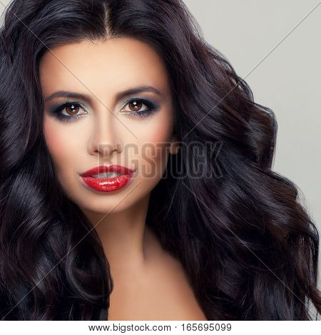 Perfect Brunette Woman Model with Healthy Curly Hair and Makeup. Beautiful Female Face