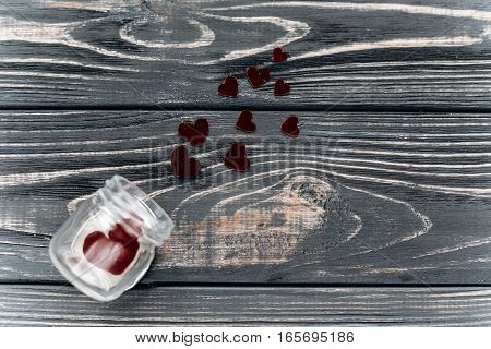 Valentine Concept. Stylish Velvet Hearts In Glass Jar Flat Lay On Black Rustic Wooden Background. Ha