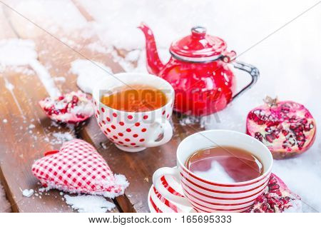 Vintage Scene with  Heart, Hot Cup of Tea on the Snow, Red Teapot, Pomegranate, Daylight, Outdoors. Copy space, Selective focus, Toned.