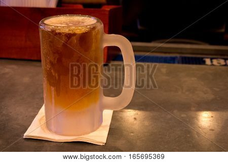 A freshly poured microbrewery beer in a frosty cold mug.