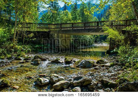Old Bridge over Sunlit Mountain Creek in Austria
