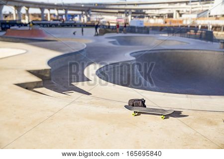 skateboard and backpack in skate park. the concept of freestyle extreme sport. blurred background due to the concept. empty space for your text
