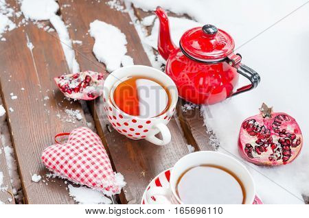 Vintage Scene with Heart, Hot Cup of Tea on the Snow, Red Teapot, Pomegranate, Outdoors. Copy space, Selective focus, Toned.