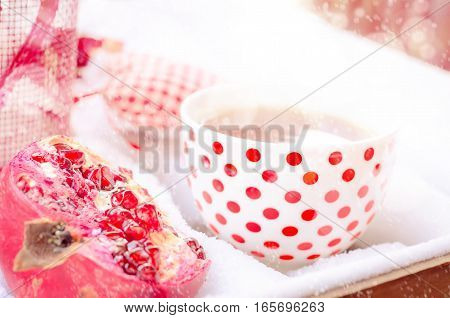 Cozy Scene with Heart, Hot Cup of Tea on the Snow, Pomegranate, Daylight, Outdoors. Copy space, Selective focus, Toned.