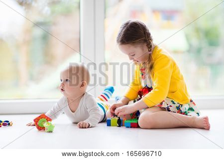 Sister And Baby Brother Play With Toy Blocks
