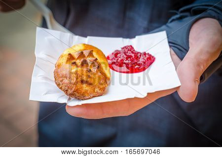 Traditional Polish street food in Zakopane, Europe. Smoked cheese with jam in a hand